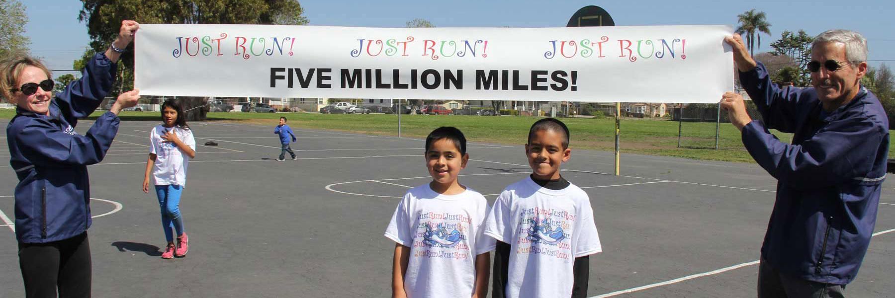 Susan and Mide holding banner with Five Million Miles above two program participants